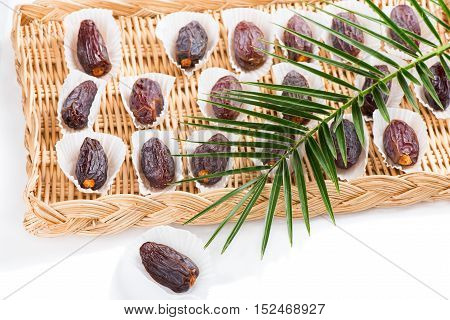 Date fruits (Medjool) in a wicker tray decorated with green leaf of palm tree isolated on white background.