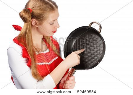 Young beautiful housewife in bright red apron with funny ponytails holding frying pan and touching its clean surface with finger isolated on white background.