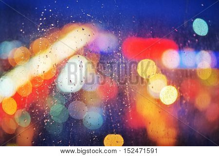 rain drops on glass window viewing city lights on a dark weather evening. raining scenery background. climate weather change concept