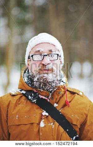 Portrait of bearded man with snow on his face.