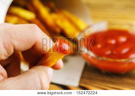 Hand holding piece of french fries with ketchup selective focus