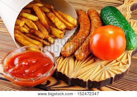 Homemade fast food portion of french fries ketchup grilled sausages tomato cucumber on wooden board