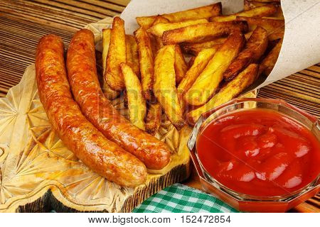 Homemade fast food portion of french fries ketchup grilled sausages wooden board