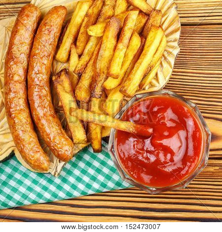 Homemade fast food portion of french fries ketchup grilled sausages tomato on wooden board