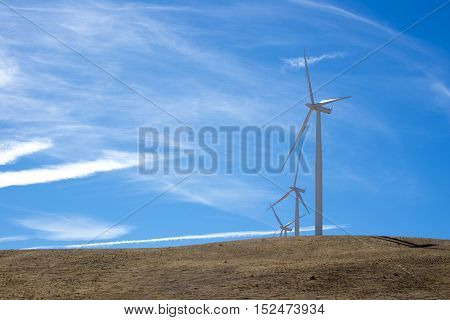 three wind turbines on top of a hill with blue sky