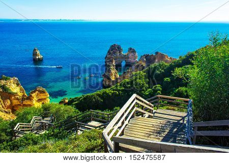 Wooden walkway to beautiful beach Praia do Camilo with cliff and rock formation Algarve region Portugal