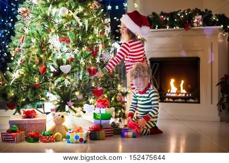 Happy little kids in matching red and green striped pajamas decorate Christmas tree in beautiful living room with traditional fire place. Children opening presents on Xmas eve. Focus on girl