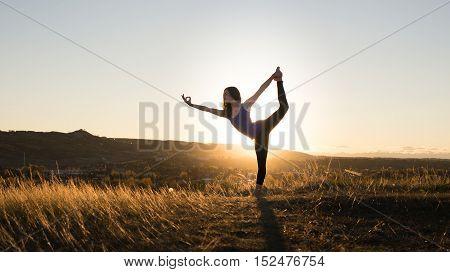 Woman doing yoga dancers pose during evening sunset
