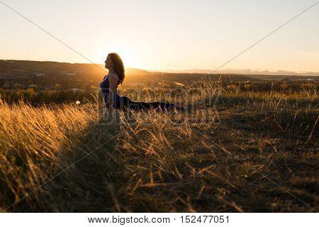 Woman doing yoga upward dog pose during evening sunset