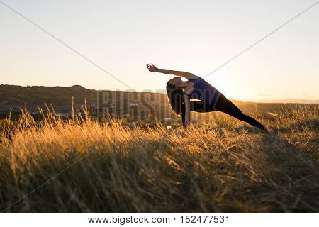 Woman doing yoga extended side angle pose during evening sunset