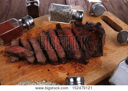 fresh roast red beef meat fillet mignon cutted on wooden plate with many different kinds of dry spices red hot paprika crushed black pepper salt dry mustard grains over table