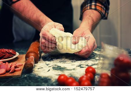dough for pizza with cherry tomatoes and basil smoked sausage