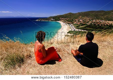 Man and woman in orange dress sitting and enjoying view on beautiful beach and blue sea with transparent water in Sarinia Italy. The beach is called Solanas Sinnai.