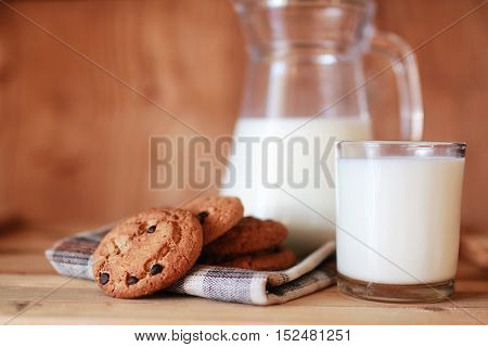 glass and carafe with fresh cow milk on a wooden table