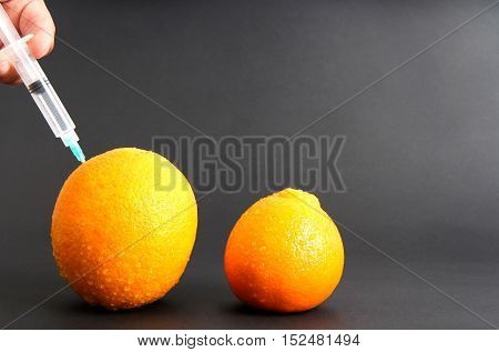 oranges with a syringe inside on a surface