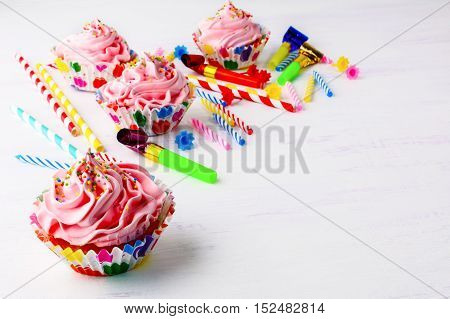 Birthday party background with decorated pink cupcakes and candles. Homemade cupcakes served for party. Birthday card background. Copy space.