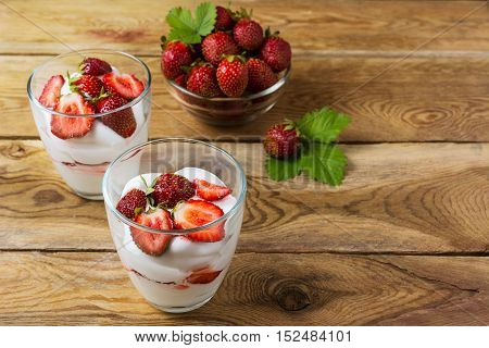 Summer layered cream dessert and ripe strawberry in glass bowl . Whipped cream with fresh strawberry.