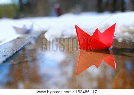 small paper folded boat origami method in a spring brook in the park