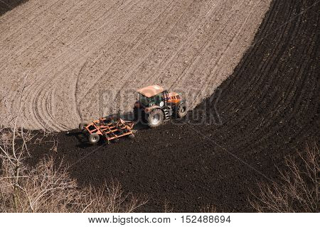 Tractor plows a field in the spring accompanied by rooks Tractor