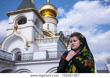 Girl near the church holds his arms