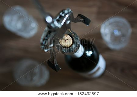 Metal corkscrew with a bottle of delicious wine and glasses for him