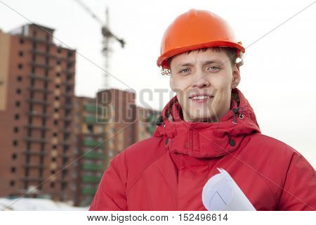 Engineer builder in helmet at construction site, near new building