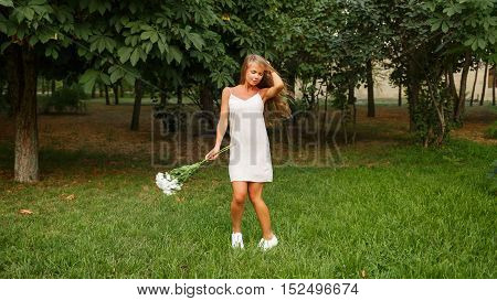 Pretty attractive girl holding a bouquet of daisies. She is in a white dress standing on a lawn in a park