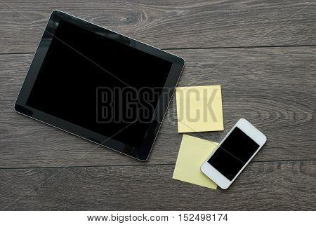 tablet with yellow sticks and phone on wooden surface