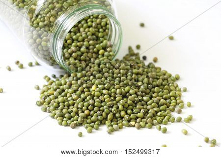 Raw green lentil in jar on white isolated background