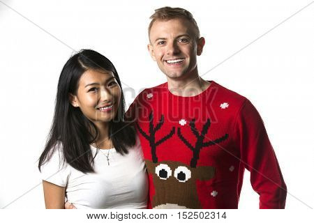 Portrait of happy multi ethnic couple wearing christmas jumpers in studio