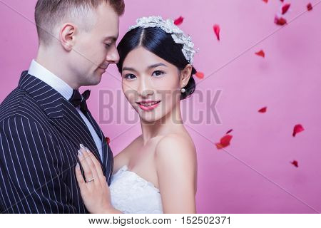 Portrait of beautiful bride standing with groom against pink background