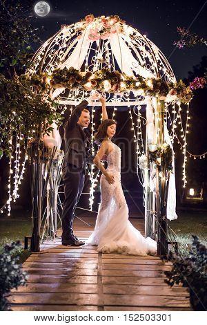 Full length of wedding couple dancing in illuminated gazebo at night