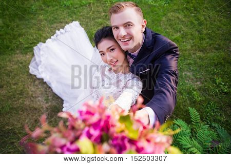 High angle portrait of happy wedding couple on grassy field