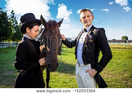 Portrait of confident man standing with horse and woman on field