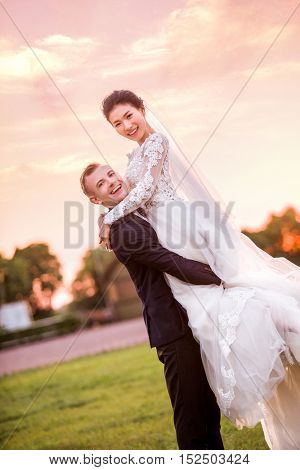 Portrait of happy bridegroom carrying bride on field during sunset