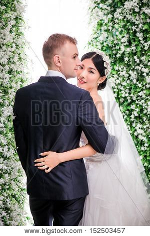 Portrait of smiling bride standing with bridegroom against flower decorations