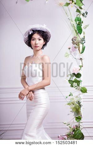 Portrait of elegant bride standing against white wall