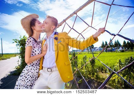 Woman kissing man while standing by fence at field against sky