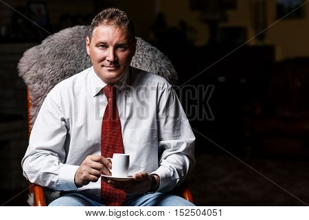 Serious middle-aged businessman with coffee cup sitting in the chair in dark room