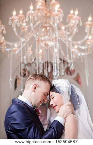 Side view of loving wedding couple standing head to head in church