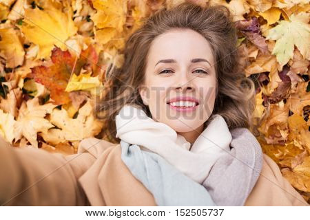 season and people concept - beautiful young woman lying on ground and autumn leaves