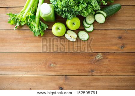 healthy eating, food, dieting and vegetarian concept - bottle with green juice, fruits and vegetables on wooden table