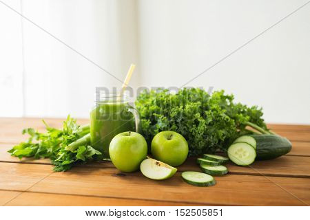 healthy eating, food, dieting and vegetarian concept - close up of glass jug with green juice, fruits and vegetables on wooden table