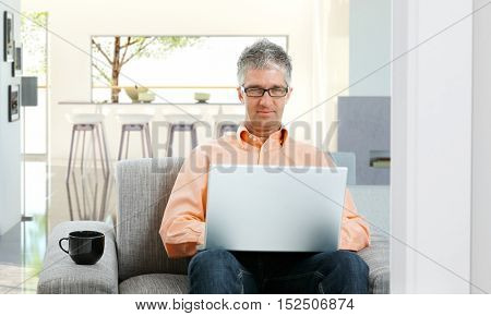 Confident caucasian mature businessman working on business at home, sitting on sofa, laptop in lap. Wearing glasses, looking at camera.