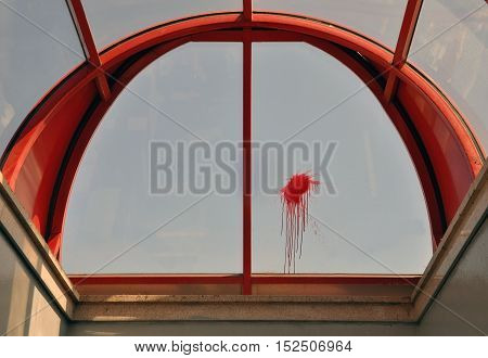 The hinged construction of red frame and a transparent fill look up. Red blot with fluid drops on the glass.