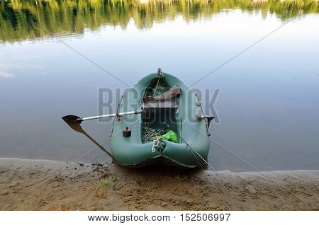 Rubber boat with fishing gear standing on a river near the sandy beach.