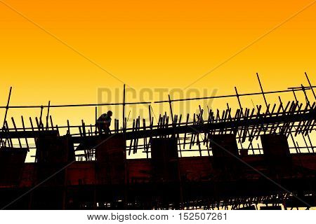 Construction site silhouettes of construction industry workers on scaffolding against the sunset light.