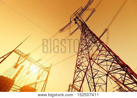 High voltage tower and power plant chimney under the twilight sky background
