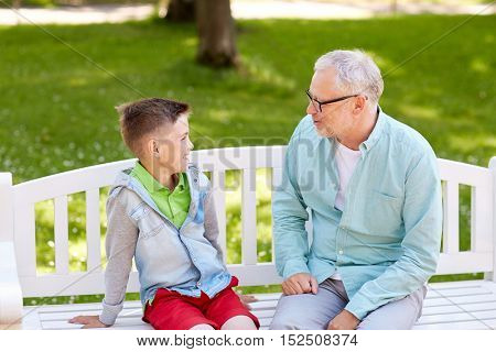 family, generation, communication and people concept - happy grandfather and grandson talking at summer park