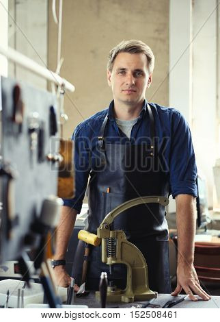 Leather craft workshop owner at his work place